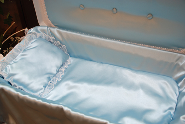 detail of deluxe white pet casket with blue bedding and upholstery