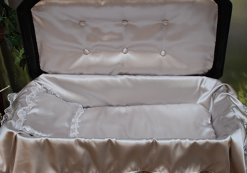 detail of deluxe black pet casket with silver bedding and upholstery