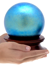 final fetch blue glass sphere cremation urn shown in hands for size scale