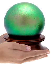 final fetch green glass sphere cremation urn shown in hands for size scale