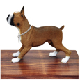 Side view of tawny white Boxer dog figurine on wooden urn
